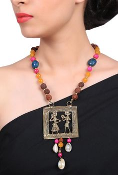 Dhokra jewelry is inspired by human figures and this necklace is a beautiful amalgamation of holy Rudraksha beads with an attractive square human figures pendant. The colourful beads are further enhancing the beauty of the exquisite piece. Adorn it with a saree or a maxi dress.  Dimension: L: 15 inch Weight: 100 gm Color: Multi-color Material: Brass Closure: Metallic lock Finish: Hand-crafted Inspiration: Dokra Heritage
