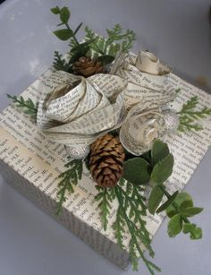 wrapping ... book paper with gorgeous book paper rolled roses and real/realistic looking pine cones and tree cuttings ...