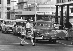 A man crossing the street carrying a UDI election poster, in Salisbury, Rhodesia.