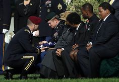 During a burial service for U.S. Army Chief Warrant Officer 2 Thalia S. Ramirez, Brigadier Gen. Charles Flynn (left) presents the American flag that covered her casket to Ramirez's husband, U.S. Army Special Forces (Green Berets) Sgt. Jesse Belbeck at Arlington National Cemetery, on September 26, 2012 in Arlington, Virginia.