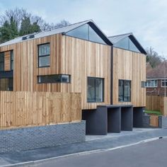 Twin wooden houses by Adam Knibb Architects are raised up above street level