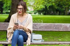 Thoughtful student girl holding phone in the park
