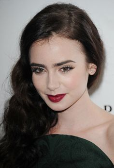 """Lily Collins living up to her """"Snow White"""" role with matte porcelain skin and wine stained lips."""