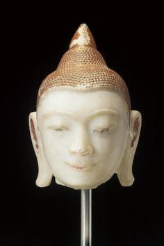 A large lacquered and gilt white marble head of the Buddha Burma, Shan States, 17th/18th Century With a serene, benevolent expression, the earlobes broad and long, the chignon rising to a tapering lotus knop,  49cm.(18in.) high