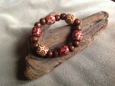 Breeze into Fall...handcrafted stretchy bracelet.  Unique, hand painted wood beads accented with two darker wood beads.  One size fits most.