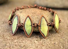 5 copper leaves are hand cut from copper, the top layer is pierced and a smaller leaf is cut out, domed, fired with transparent yellow over opaque green for a speckled chartreuse look.  hand wrapped c
