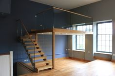 Split level living and dinning room with mezzanine study in converted listed mill. Oak staircase and floor and frameless glass balustrades