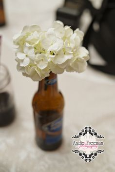 Beer bottle with hydrangeas Photography: www.TheAthensWeddingPhotographer.com Planning, Floral, and Event Design: www.WildFlowerEventServices.com Venue: Dillard, Ga