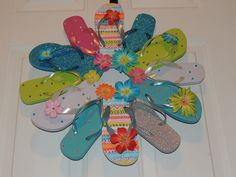 """Flip Flop Glittery Sun Fun, Decorate your door or room with the summer footwear we love to wear. This wreath is fastened with greening pins making it sturdy and heat resistant. The wreath measures approximately 22"""" across, includes 12 flip flops and comes with a variety of flower embellishment's and rhinestones. Please avoid displaying this wreath in between a storm and house door. Too much direct sunlight causes extreme heat built up."""