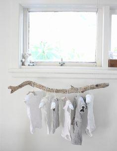 Snoezig, baby kleertjes opgehangen aan een drijfhouten tak