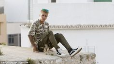 Take a break: Justin took a seat on the edge of a wall and looked in a pensive…
