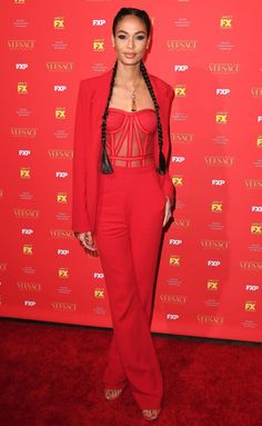 Joan Smalls in a red strapless bustier jumpsuit and blazer