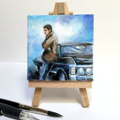 "I loved painting this tiny 3x3"" canvas of Dean Winchester, leaning on his Baby, the Impala.     Lots of texture and painterly brushstrokes in this pretty miniature acrylic painting, with vibrant blues, lilacs and shades of black. Just a really stunning piece. Comes with an actual miniature wooden artists display easel! So cute!  *I will be reproducing this art on prints sometime in the future.   One of a kind. Signed.     Great to display your love of Supernatural at your office desk or at…"