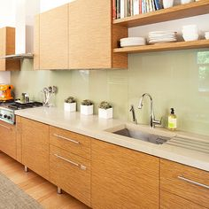 The owners of this contemporary kitchen decided to use large panels of soft green glass as a backsplash because it reflects the leafy views outside. Zebrawood laminate cabinetry and beige-flecked concrete countertops complete the earthy look..