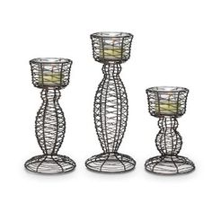 Cleverly coiled from wire, our candleholders have a charming rustic appeal. Includes three flared glass cups for use with votives or tealights. Without glass cups, use with large tealights. Candles sold separately. One of each size: 10 1/4h, 8h, 6h.