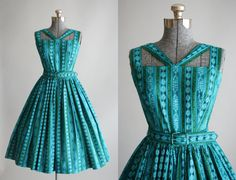 This 1950s cotton dress features a floral and striped print in shades of turquoise, green and blue. The dress has an amazing strap detailing