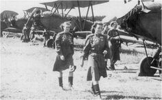 "Pilots of the 588th Night Bomber Regiment, a ka the ""Night Witches,"" walk in front of a line of Po-2s at a Soviet air force base in 1944."
