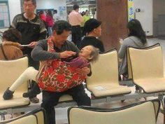 """The Forgotten Ones: Compassion for the Elderly """"The picture was taken at a hospital in Taiwan. His mom had leg fractures that she felt very uncomfortable sitting on the wheelchairs. The gentleman recalled that his mom used to carry him on the back when he was a child, so he found a cloth to take his mom to see the doctor.   Years earlier, he had refused a career promotion that required a relocation just so he could take care of his mom."""" ~ Philip Lee"""