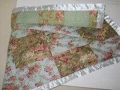 This handmade pieced quilt is sewn from the famous Robin Pandolph cotton fabric, in colors of olives, sage greens and aqua blues. All cotton, filled with the finest poly batting and the back is made from a soft flannel fabric with light green motives on it. All bound in matching satin blanket binding. Washable…. Measurements: …