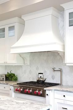 An Wolf integrated gas cooktop positioned against marble arabesque backsplash tiles between white shaker cabinets topped with a gray and white quartzite countertop fitted with a deck mount pot filler.
