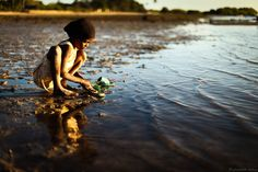 A young village girl washes her sandals in the warm waters of the Indian ocean. No people on earth have fascinated me like the villagers of Kenya's Funzi Island. Without cars, roads, electricity, internet, or running water, they seem to me the richest folk in the world. (Photo by Elisabeth Mulroy)