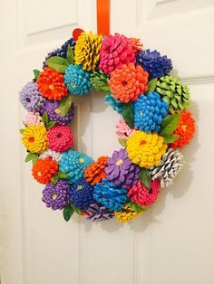 Painted Georgia Pinecone Zinnias Wreath. Each wreath will be painted in Spring and Summer colors and will be reminiscent of a real zinnia flowers. Each Pinecone is descaled and hand cut, painted and then wired upside down to look like a Zinnia, some greenery will be added also to