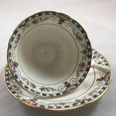 "Vintage Aynsley Teacup and Saucer, Rosebuds and Urns Widemouth Blue, Pink, Gold This lovely vintage set is in excellent condition No chips cracks or crazing Slight gold wear on handle as in picture Measures Cup opening 3.75"" Including handle 4.75"" Saucer 5.5"" Combined Shipping"