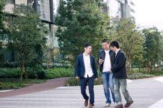 3 つの人はスマートフォンを見に歩道 stock photo