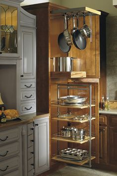 A class act among cabinets, the Utility Storage Cabinet with Pots and Pans Rack features a space to hang pots and pans from the top, four pullout storage shelves on the bottom, as well as a stationary storage shelf in the middle.
