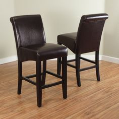 Constructed with durable wood with faux leather upholstery, this set of two counter stools is offered in a variety of colors and feature a dark walnut-finished base. The shape of the seats are designed to add stability.