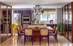 Integrada ao living, a cozinha tem acabamentos sofisticados. Mas o que chama a atenção é a escolha ousada do cooktop inserido na mesa de teca, que contrasta com as cadeiras roxas. Projeto da arquiteta Maricy Borges