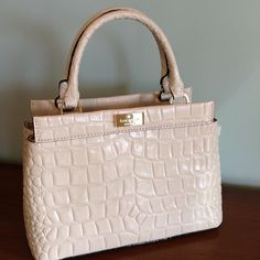 Kate Spade Leather Croc Tote NWT   Beautiful Cream colored Croc embossed leather tote from Kate Spade! Very dressy with gold nameplate on the front & small-med. size to take you to your dressier summer occasions . This off white color will be perfect for all your functions & easily transcends from day to night in a moments notice. Rolled handles with Kate Jacquard lining plus 1 zip wall pocket & 2 organizer pockets. Magnetic snap closure . Comes with handwritten Saks tag for 600.00 retail…