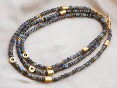 1348118N | Never-the-same-necklace-twice! Eye-catching triple wraparound necklace of small faceted, blue-flash labradorite cubes, asymmetrically embellished with 24K matte vermeil cylinders, globes, and spacers.  Can be worn as glittering opera length, or draped one or 2 times as an ever-new multi-strand necklace, for the relationships between the gold accents are always changing. Closed with a 24K matte vermeil toggle clasp. $595