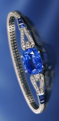 An Art Deco sapphire & diamond bracelet, Cartier, French, ca 1925, centering a cushion-cut sapphire, joining a slender looped line of old European & single-cut diamonds, accentuated by calibré-cut sapphires; signed Cartier Paris London New York, no. 4262, with French assay mark & maker's mark for Renault, within original fitted box; sapphire weighing approx 17.20 cts; est total diamond weight: 2.60 cts; mounted in platinum; length: 7 1/4in.