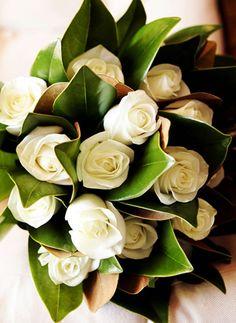 Magnolia leaves and cream roses.