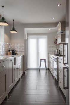 Subway tile. Dark grout. Barn lighting. Marble countertops. Farm sink. What's not to like?