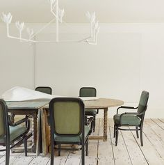 Rustic inspired dining space with a white chandelier and green dining chairs