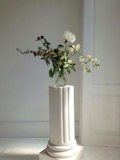 Peoni arrangement atop porcelain pillar.