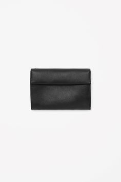 Made from smooth, soft leather with modern raw-cut edges, this simple purse has a foldover fastening that is secured with a hidden magnet. Designed for everyday use, it has three inside compartments, four card slots and a separate zip pocket for coins.