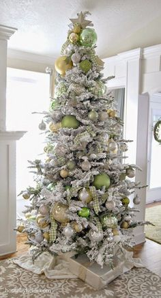 A flocked Christmas Tree dressed in soft Golds and Greens.