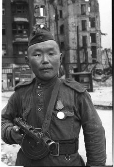 From Mongolia with love: Red Army soldier from the farthest steppes of the Soviet Union poses triumphant in the devastated streets of Berlin, May 1945.