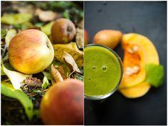 Fallobst Äpfel im Laub und ein Glas Grüner Smoothie mit einem aufgeschnittenen Muskatkürbis daneben.