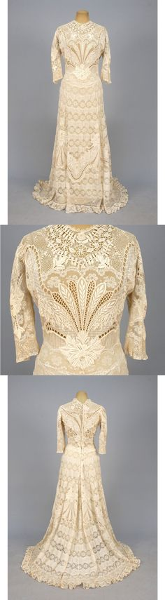 TRAINED LACE and EMBROIDERED SUMMER GOWN, EARLY 20th C. Cream cotton having elbow length sleeve lavishly decorated with padded embroidery, eyelets and insertions of various laces, full trained skirt with serpentine bands of Val lace and tucks.