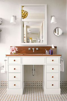 Give a gently used desk new life as a sink console with high-gloss white paint and amber glass hexagonal knobs.