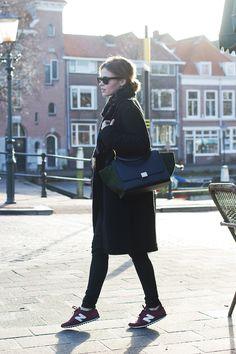 so chic. new balance trainers. celine bag. black over coat. black skinnies.