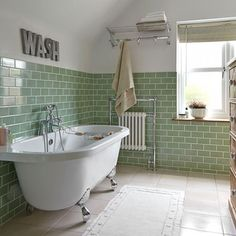 Green tiled bathroom with rolltop bath
