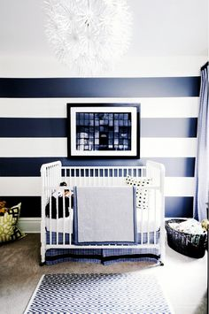 Striped child's room with white crib and unique chandelier