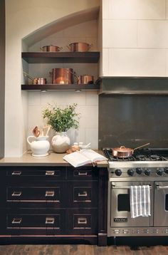 A collection of copper pots on open shelves draws attention to the dramatic stove in this upscale country kitchen designed by Nam Dang-Mitchell. Kitchen Stove, Kitchen And Bath, New Kitchen, Kitchen Dining, Kitchen Cabinets, Black Cabinets, Kitchen Black, Distressed Cabinets, Distressed Kitchen