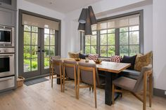 A built-in banquette in the kitchen doubles as a window seat with an array of pillows in three different patterns. The chunky, country-style dining table has room to seat five more around the table, and beautiful gray French doors allow easy access to the backyard.