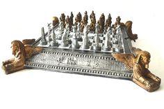 Suntuoso jogo de xadrez italiano no estilo egípcio, no formato piramidal, com trabalhos em relevo de hieróglifos e cenas do cotidiano da região, adornado com cantoneiras com figuras estilizadas de Tutankamon de asas. Estrutura em resina patinada nos tons prata e dourado. Completo, com todos as peças  representando as divindades, como: Athenon, Gato, Eurípedes, etc.. Estrutura no feitio de caixa. Peças acopladas em estojo de veludo interno. Med.: 72 X 72 cm.  Acompanha um livro de Técnicas e…